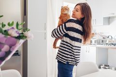 Young woman playing with cat in kitchen at home. Girl holding and raising red cat. Happy master having fun with her pet royalty free stock photos