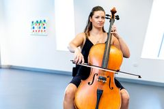 Woman playing cello. Young woman playing a cello royalty free stock photos