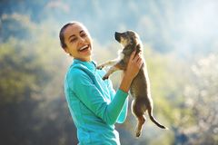 Young woman playing with a cute little puppy on a green grass in the camping. Young woman is playing with a cute little puppy on a green grass in the campsite royalty free stock image
