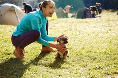 Young woman playing with a cute little puppy on a green grass in the camping. Young woman is playing with a cute little puppy on a green grass in the campsite stock photos