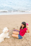 Young woman playing with dog. Young beautiful asian woman playing with dog on beach near sea Stock Photography
