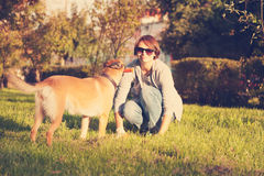 Young woman playing with dog outdoors in the park. Stock Images