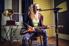 Young woman playing the eletric guitar and singing Royalty Free Stock Photo
