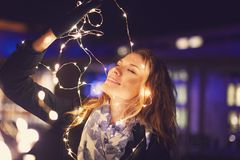 Young woman playing with fairy lights eyes closed. At winter outdoor in city royalty free stock photography