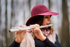 Young woman playing flute outdoor Stock Photography