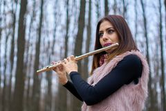 Young woman playing flute outdoor Stock Image