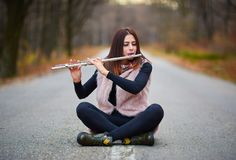 Young woman playing flute. While sitting in the middle of the road Royalty Free Stock Images
