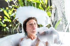 Young woman playing with foam in bathtub. Tropical bathroom in luxury villa, Bali island, Indonesia. Royalty Free Stock Image