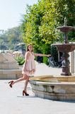 Young woman playing with a fountain Stock Photos
