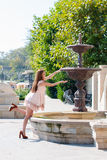 Young woman playing with a fountain Stock Images