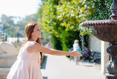 Young woman playing with a fountain Stock Photography