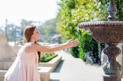 Young woman playing with a fountain Stock Photo