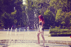 Young woman is playing at a fountain Royalty Free Stock Photo