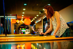 Young woman playing a game of air hockey Royalty Free Stock Images