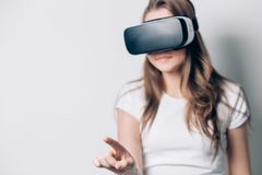 Young woman playing game in virtual reality glasses, VR headset glasses device. Stock Image