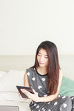 Young woman playing games on tablet Stock Photo