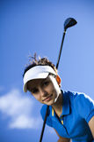 Young woman playing golf Stock Images