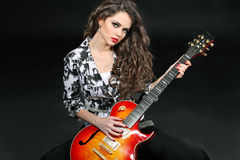Young woman playing on guitar on black Royalty Free Stock Photos