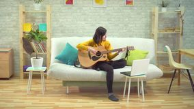 Young woman playing guitar, learning on the internet, in modern apartments