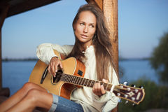 Young woman playing guitar outdoor on sunset. Young woman playing guitar in summerhouse on sunset Royalty Free Stock Image