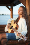 Young woman playing guitar outdoor on sunset. Young woman playing guitar in summerhouse on sunset stock photography