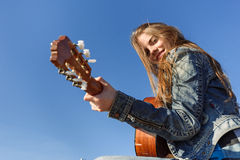 Young woman playing guitar outdoor Royalty Free Stock Image