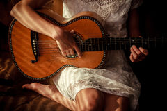 Young woman playing guitar with shadows from venetian blinds Royalty Free Stock Images