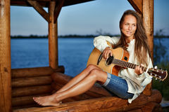 Young woman playing guitar in summerhouse Stock Photography