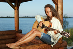 Young woman playing guitar on sunset. Young woman playing guitar in summerhouse on sunset Royalty Free Stock Image