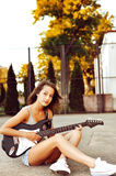 Young woman playing guitar on sunset Royalty Free Stock Images