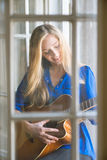 Young woman playing guitar on window Royalty Free Stock Photo