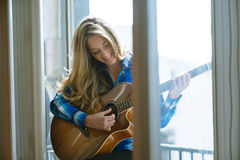Young woman playing guitar on window. She is smiling and looking into guitar Stock Photos
