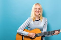 Young woman playing a guitar. On a solid background Royalty Free Stock Photography