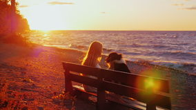 Young woman playing with her Australian Shepherd in the park. Sitting on a bench on a background of an orange sky at stock video