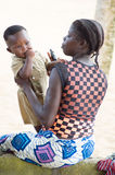 Young woman playing with her baby. Abidjan, Ivory Coast - 29 August 2015: young woman sitting with her baby looks at the play, his finger in his mouth Stock Photo