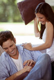 Young woman playing with her boyfriend. Young women playfully hitting her boyfriend with a cusion Royalty Free Stock Images