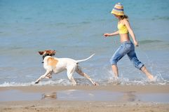 Young woman playing with her dog. On the beach Stock Photo