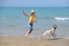 Young woman playing with her dog. On the beach on a summer day Stock Image