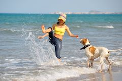 Young woman playing with her dog. On the beach on a summer day Royalty Free Stock Photos