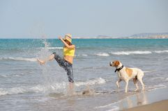 Young woman playing with her dog on the beach. On a summer day stock image