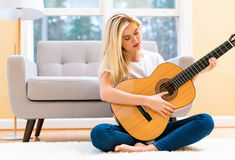Young woman playing her guitar Stock Photography