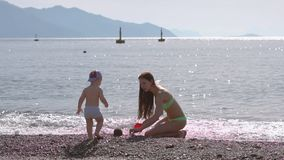 Young woman playing with her son on the beach by the sea in slow motion stock footage