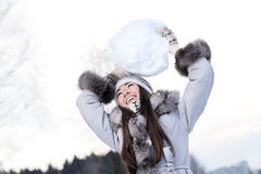 Young woman playing with huge snowball Stock Photos