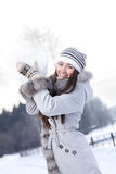 Young woman playing with huge snowball Stock Photo