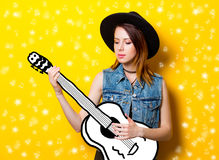 Young woman playing on imagination guitar. On yellow background Stock Photo