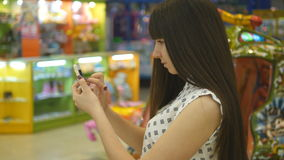 Young woman playing indoor at shopping center, using smart phone. Girl play the popular smartphone game - catching. Pokemon in hypermarket mall stock video footage