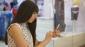 Young woman playing indoor at shopping center, using smart phone. Girl play the popular smartphone game - catching stock footage
