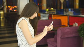 Young woman playing indoor at shopping center, using smart phone. Girl play the popular smartphone game - catching. Pokemon in hypermarket mall stock footage