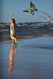 Young woman playing with kite on the beach Royalty Free Stock Images