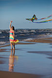Young woman playing with kite on the beach Stock Images